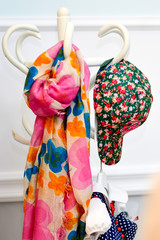 Multicolored colorful scarf and cap hanging on hanger
