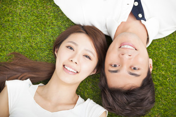 Top view of young couple  lying together on the grass