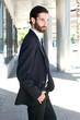 Young businessman walking outside in business suit