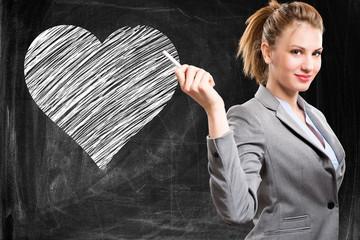 Woman in front of an heart drawn on a blackboard