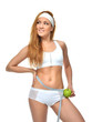 happy female measuring waist with tape measure and green apple e