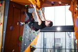 Young man practicing rock-climbing in indoor climbing gym