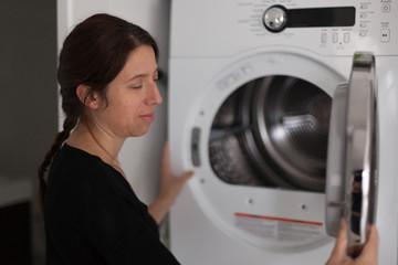 Profile of mid adult woman using a washing machine