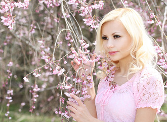 Girl with Cherry Blossom. Spring Flowers. Beautiful Blonde Young