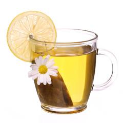Cup of chamomile tea with chamomile flower, tea bag and lemon