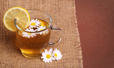 Cup of chamomile tea with chamomile flowers and lemon