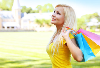 Happy young woman with shopping bags. Outdoor