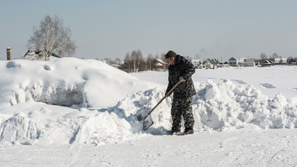A man in camouflage clothing removes snow shovel