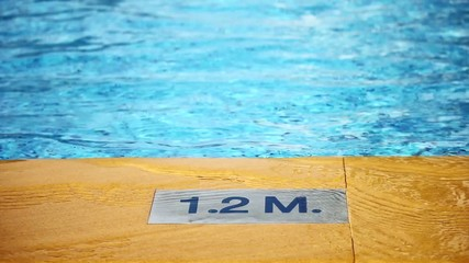 Depth marking on pool edge and water waves in swimming pool