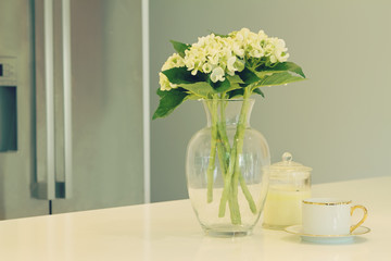 Glass vase of white flowers and teacup in a kitchen with blurred