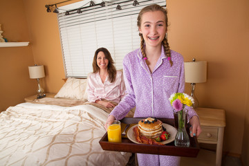 teenage girl serving Mom breakfast in bed