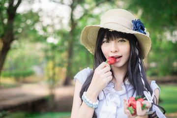 A cute Asian Thai girl with vintage clothings is eating strawber
