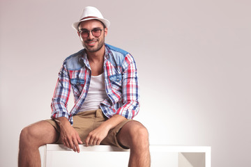 Casual young man sitting on a white table