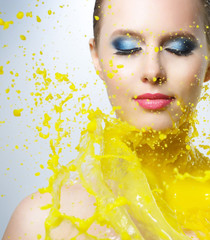 Beautiful girl and yellow paint splashes