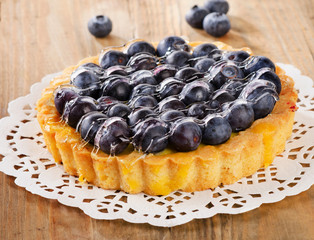 Tasty homemade pie with blueberries  on a wooden table