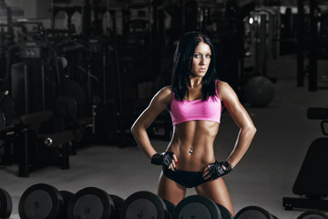 sexy fitness young woman resting in gym after exercises