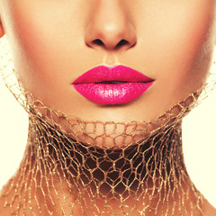 Female lips with pink lipstick and golden veil on the neck. clos