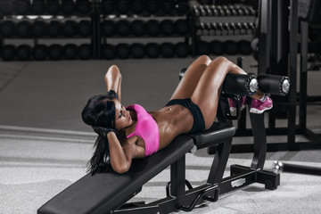 athletic brunette girl doing some crunches in a bench at the gym