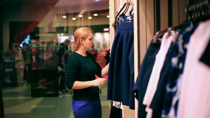 Woman shopping clothes. Shopper looking at clothing indoors in