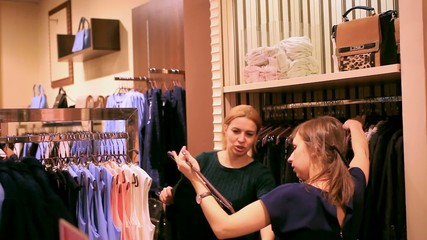 shop worker advises and assists young woman chooses some clothes