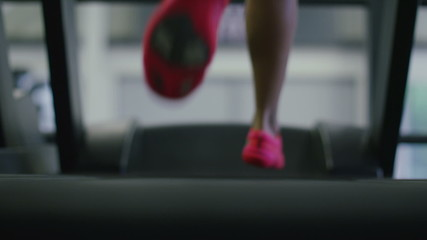 Young woman running on a treadmill in slow motion