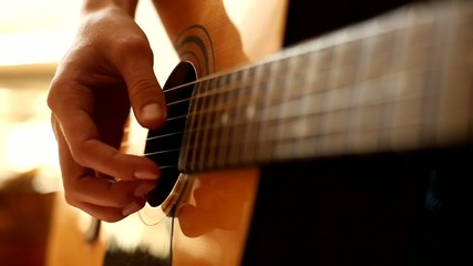 Female hand playing on acoustic guitar. Close-up.