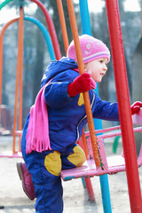 Two years old girl sitting on playgrounds swing
