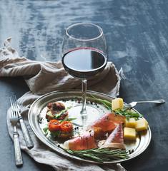Wine appetizer set. Glass of red wine, brushetta, parmesan, meat