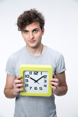 Handsome male student with big clock over gray background