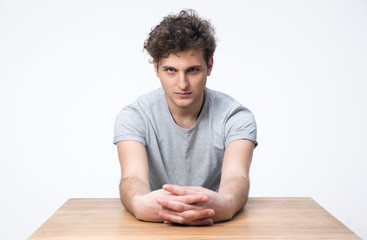 Handsome young man sitting at the table and looking at camera