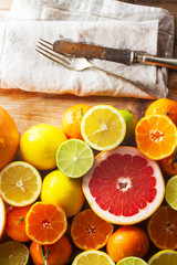 Pink grapefruit and other citrus fruit against wooden background