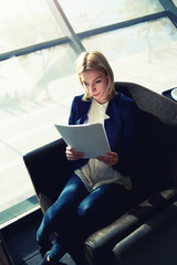 Young businesswoman examining paperwork in light office