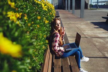 Young student girl sitting in front of a laptop at campus