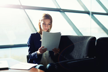 Female managing director examining paperwork in light office