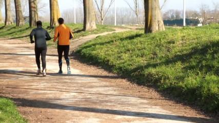 Due podisti corrono nel sentiero del parco urbano, slow motion