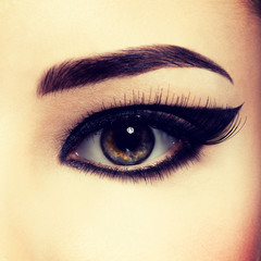 Closeup female eye with creative fashion make-up. brown eyeshado