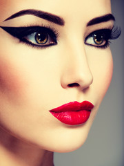 Сlose-up portrait of a woman with red lips and black make-up lo