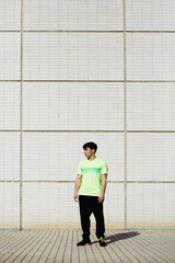 Young athletic man standing against white brick wall background