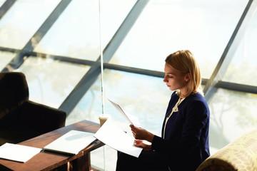 Business woman examining paperwork sitting in modern restaurant