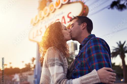 Fototapeta romantic couple kissing in front of vegas sign