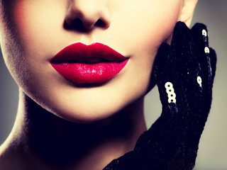 Сlose-up women's lips with red lipstick and black gloves on che