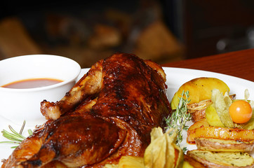 The baked half of duck with a potato, apples and pineapple