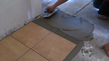 Man hand spread adhesive material. Laying floor tiles. Closeup