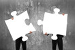 Leinwanddruck Bild - Two business people assembling white jigsaw puzzles with concret