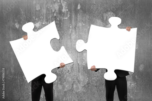 Leinwanddruck Bild Two business people assembling white jigsaw puzzles with concret