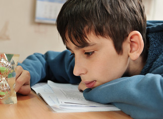 boy doing homework and looking on the hourglass