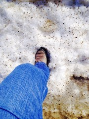 foot on dirty snow bank