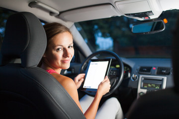 Pretty, female driver using her tablet computer