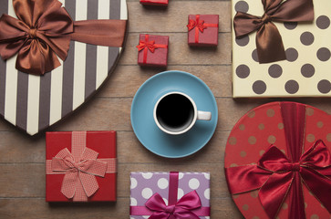 Cup of coffee and gifts around