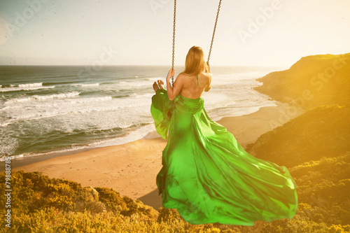Woman on a swing above the beach - 79888785